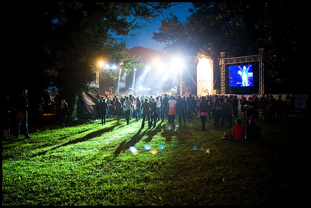 Crowd walking across grass at night towards a stage at INMusic Festival in Croatia.