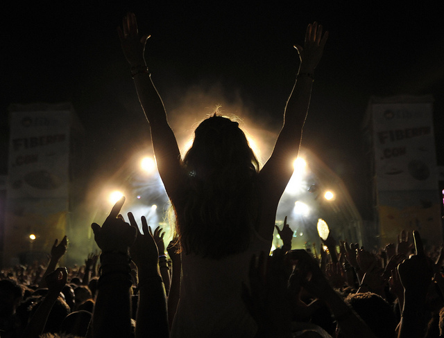 A girl sitting on shoulders in crowd with arms raised at Benicassim Music Festival in Spain