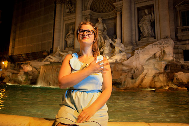 Trudy throwing a coin over her shoulder into the Trevi Fountain.