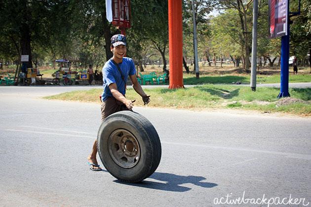 Man rolling wheel in Myanmar.